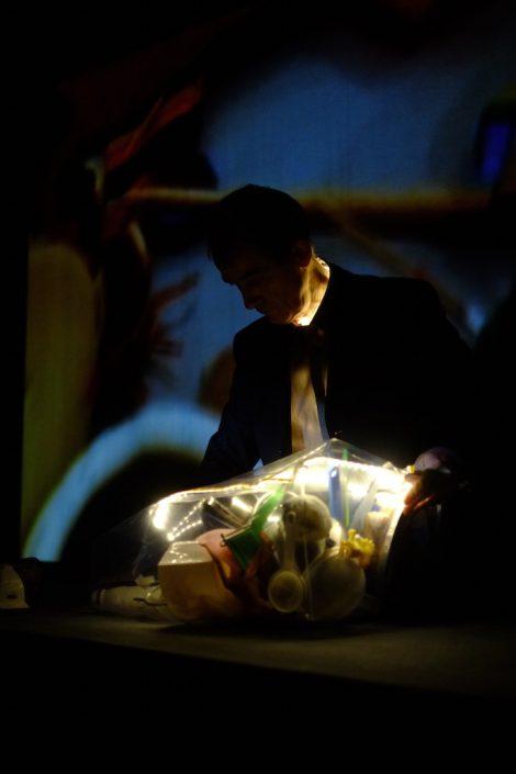 Répétitions Main tenant le passé. Pierre Fourny vide son sac (d'objets) dans la pénombre. Photo Emmanuel Pierrot. Fère-en-Tardenois.2015